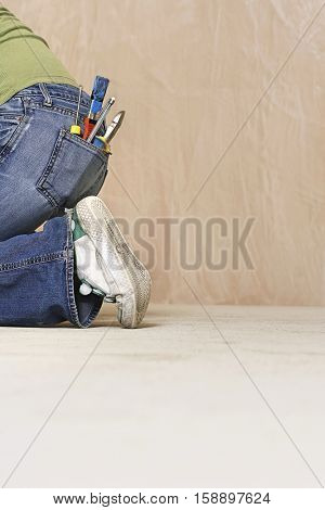 Side view lowsection of a woman with paintbrush and hand tools in back denim jeans pocket