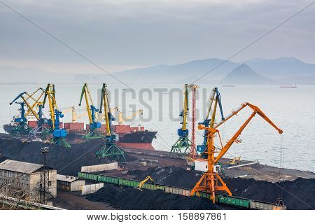 Coal terminal in the port. Heap of coal and ships on background. Top view.
