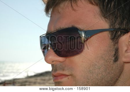 ocean reflection in the sunglasses of a young man