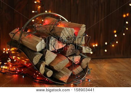 Stack of firewood and garland on wooden background