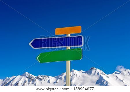 Alpine winter mountain landscape with arrow signs. French Alps covered with snow in sunny day. Val-d'Isere, Alps, France