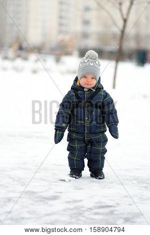 Winter portrait of toddler boy in warm coat outdoors