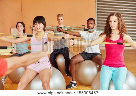 Pilates class during stretching exercises with bands at fitness studio