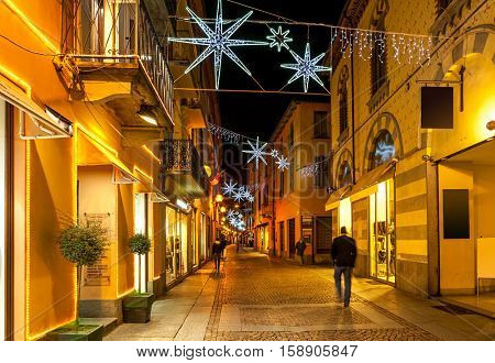 ALBA, ITALY - DECEMBER 03, 2010: Pedestrian street and shops in old town of Alba illuminated for Christmas and New Year holidays. This area is very popular with locals and tourists visiting the town.