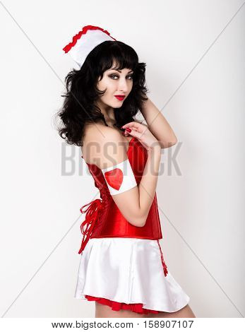 young beautiful woman dressed as nurse, medical carnival costume, she holding a stethoscope.