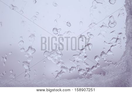 Ice water drops on winter glass. Frost patterns on window. Frosty natural pattern on winter window. Ice on a window background texture. Light frozen window glass background.