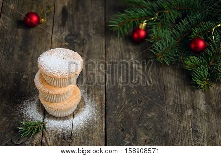 Three homemade muffins for Christmas on the old wooden background. Christmas concept. Copy space composition