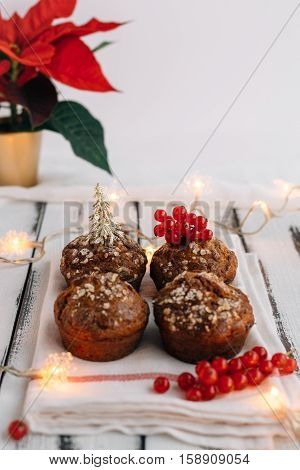 Festive Christmas Muffins on Shabby Chic White Table with Christmas Fairy Lights