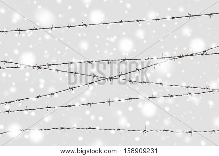 imprisonment and restriction concept - barb wire fence over gray sky and snow