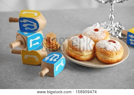 Composition of tasty donuts and dreidels on light table
