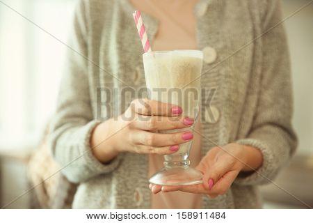 Woman holding tasty milk shake, closeup
