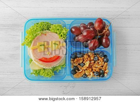 Fancy sandwich, grape and nuts in lunchbox on light wooden background