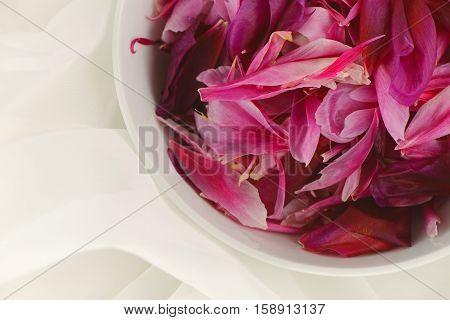 Close-up of a bowl with pink peony petals on white tulle