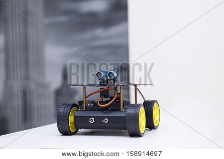 metal robot on wheels is on the table