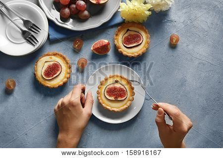 Woman with fork and knife ready to eat fig cake, top view