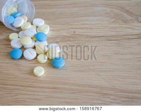 Closeup group of medicine pill on wood background pharmaceutical theme (Selective focus)
