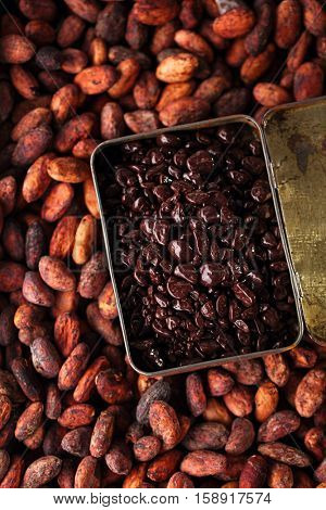 chocolate drops and roasted cocoa chocolate beans  wood background