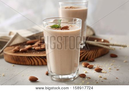 Glass with delicious nut milk shake on table, closeup