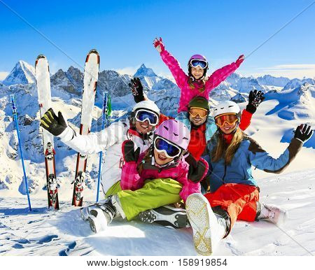Skiing family enjoying winter vacation on snow in sunny cold day in mountains and fun. Switzerland, Alps. Composite photo.