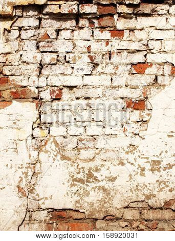 Grunge background with texture of old brick wall painted cracked paint of white color