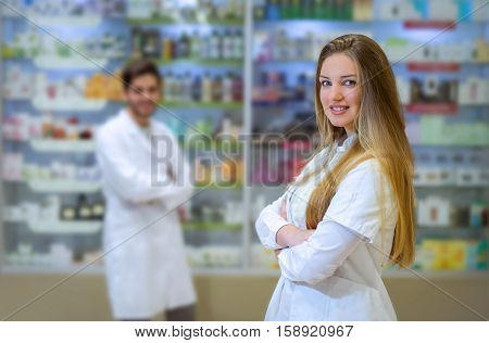 Happy young woman pharmacist over drugstore background in the background is a man pharmacist