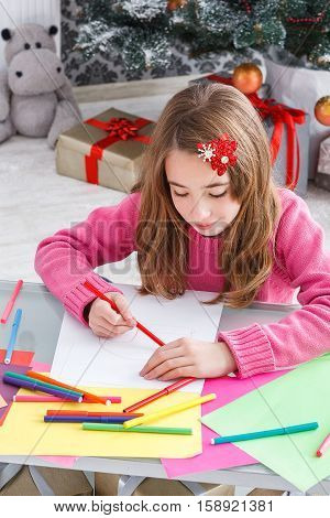 Writing letter to santa. Beautiful girl makes wish list of presents for christmas. Waiting for gift. Prepare for winter holidays