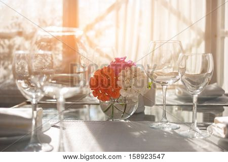 Empty wineglasses on tablecloth. Vase with flowers on table. Invite family for lunch. Aroma of geranium.