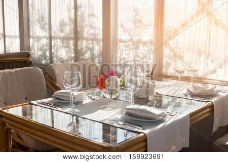 Table with plates and wineglasses. Table and chairs beside window. Invite your friends for breakfast. Cleanliness and perfect order.