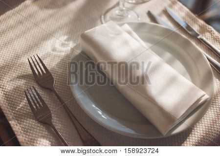 White napkin and plate. Forks and knives on tablecloth. It's breakfast time. The absolute cleanliness.