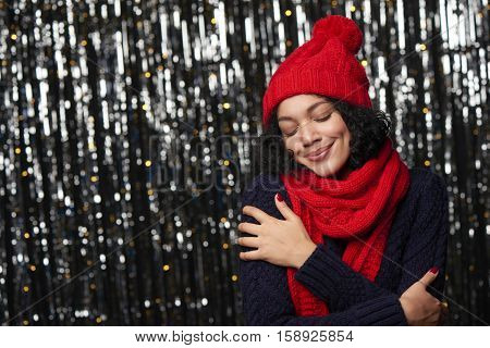 Christmas girl, young beautiful smiling wearing red knit hat and scarf over shiny background enjoying with closed eyes