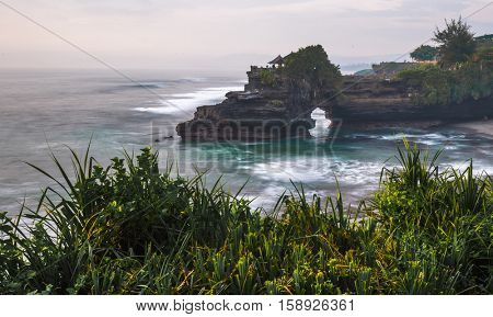Tanah Lot Temple with green plant on the foreground, Bali, Indonesia