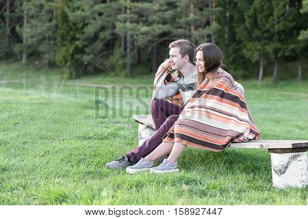 Loving couple sits on the bench over wonderful spring landscape