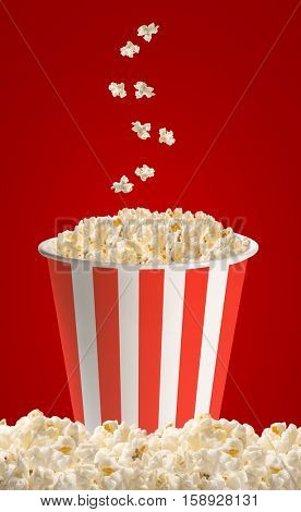 Popcorn in classic striped bucket on red background