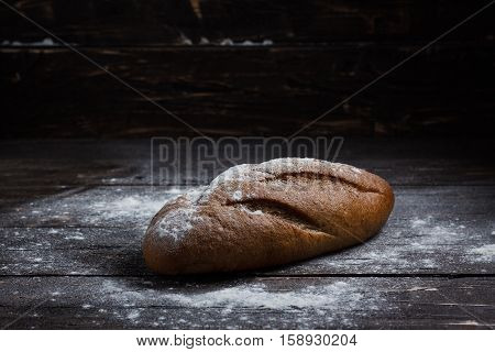 One Black Bread With Flour On A Wooden Background. Advertising Bread. Leaning Flour.