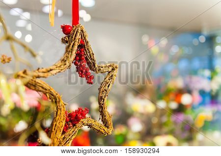 Wooden star of branches with clusters red berries hanging on the tape or ribbon other decorations and garlands.