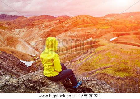 woman hiker on the trail in the Islandic mountains. Trek in National Park Landmannalaugar, Iceland