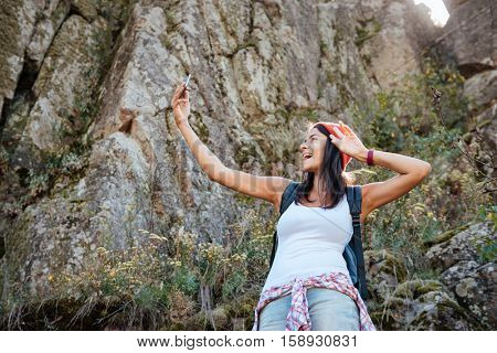 Traveling woman with backpack makes selfie near the rock