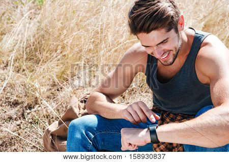 Close up portrait of a smiling young man resting outdoors and using smart watch