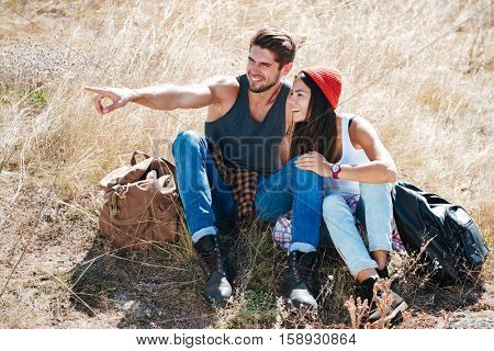 Smiling young couple resting together oudoors and pointing finger