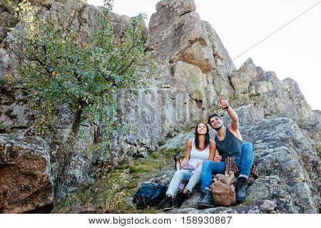 Young active couple enjoying view from top of a mountain and pointing finger