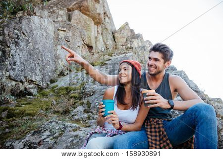Close up portrait of two young hikers having coffee break while sitting on a hill