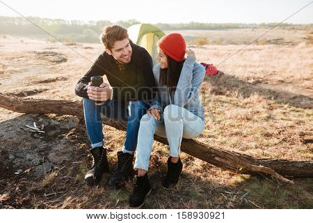 Couple near the tent. sitting on a log