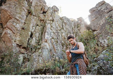 Traveling man with backpack near the rock looking at wristwatch