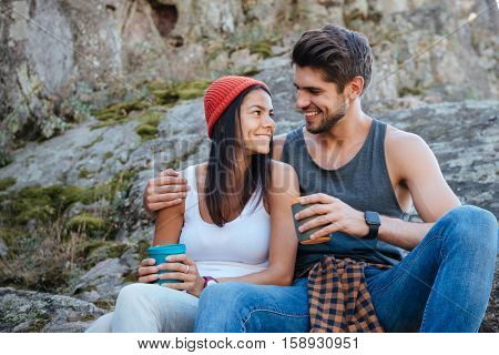 Happy couple sitting on rock and looks into each other's eyes