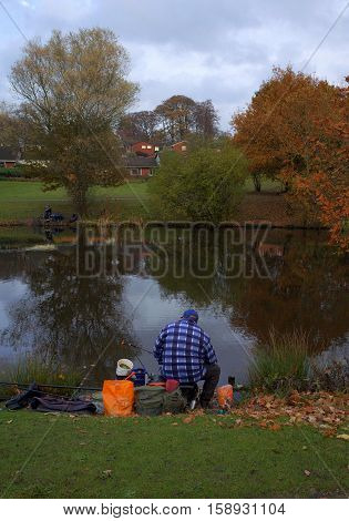 Bracknell,England - November 23, 2016: People fishing with rod and reel on the banks of a public lake on a cloudy November day in Bracknell, England