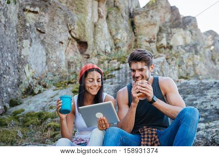 Portrait of a smiling young couple having a break from hiking and using tablet computer