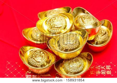 Stack of Chinese Gold Ingots on red Background.