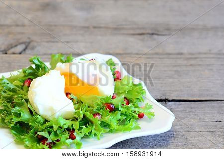 Poached egg, lettuce leaves with pomegranate seeds and olive oil. Healthy salad on a plate on wooden background with copy space for text. Healthy diet egg recipe. Closeup