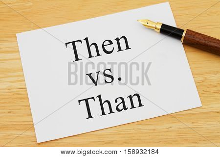 Learning to use proper grammar A white card on a desk with a pen with words Then vs Than