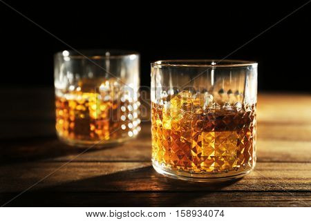 Glasses of whisky on wooden table closeup